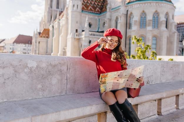 Turista femminile abbastanza francese che esplora la vecchia città europea con la mappa