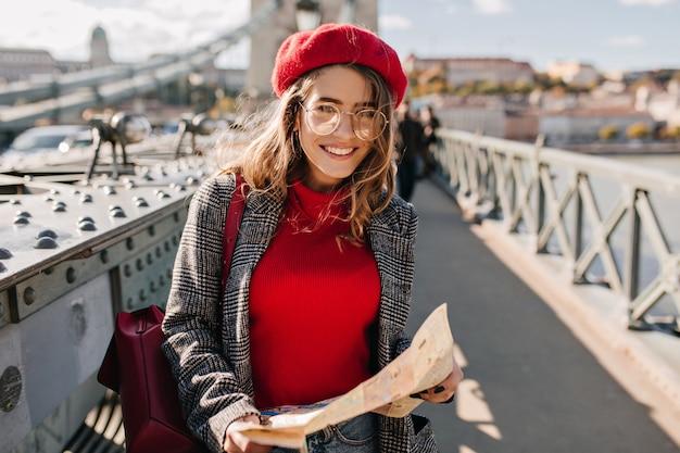 Довольно французская женщина с картой города идет по мосту в солнечный день