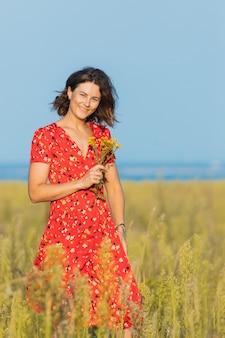 緑の野原で野外を歩いていると黄色の花の花束を持ってかなり夏の赤いドレスを着ているかなり新鮮な若い女性。村での夏休みのコンセプトとライブスタイル