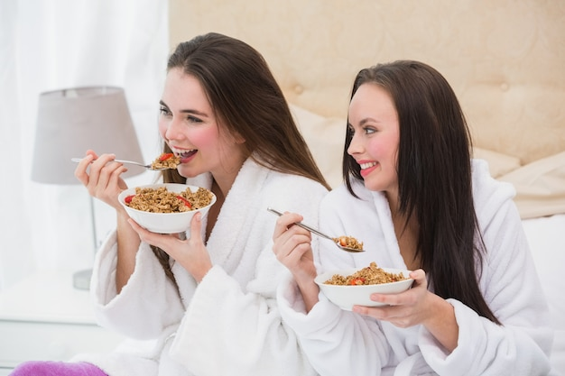 Pretty friends wearing bathrobes eating cereal