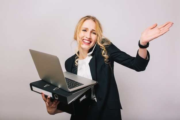 Pretty funny blonde businesswoman in suit with laptop, folder, box in hands talking on phone isolated. stylish office worker, being busy, having fun
