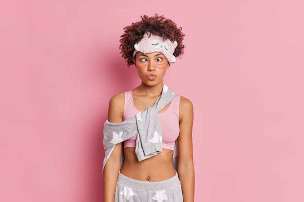Pretty funny curly haired afro american woman keeps lips folded crosses eyes and makes funny grimace dressed in nightwear poses against pink wall