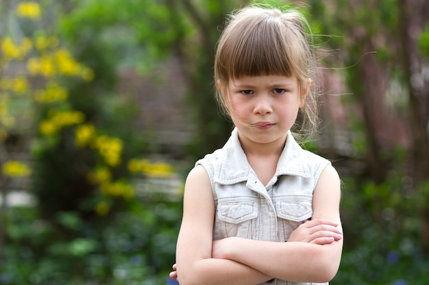 Pretty funny moody little blond preschool girl in white sleeveless dress looks into camera feeling angry and unsatisfied on blurred summer background. children tantrum concept.
