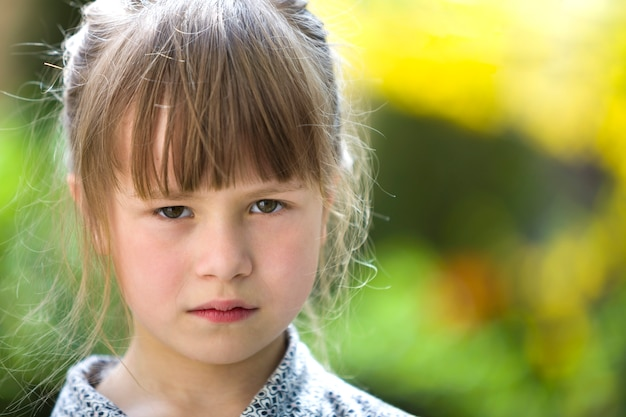 Pretty funny moody young child girl outdoor feeling angry and unsatisfied on blurred summer green . children tantrum concept.