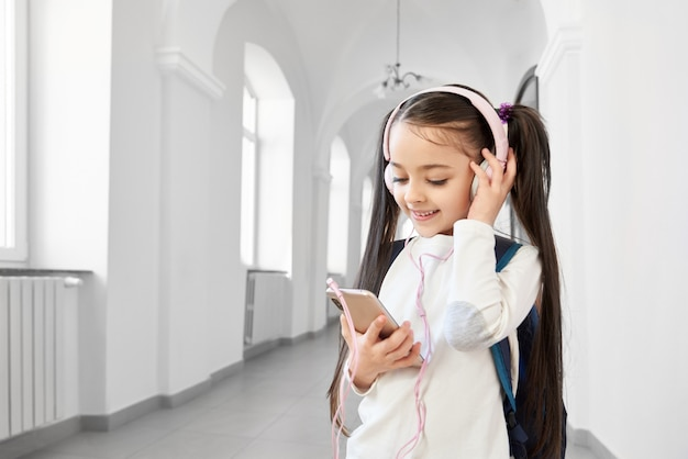 Pretty, funny schoolgirl in white sweatshirt with headphones holding pink phone.