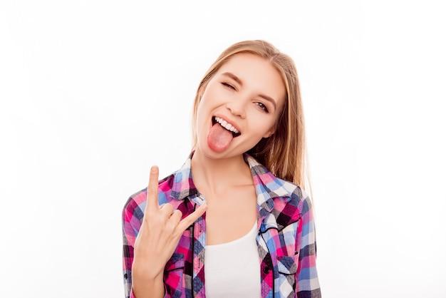 Довольно забавная молодая девушка показывает язык и рок жест