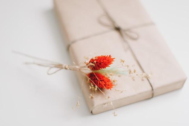 Милая подарочная коробка обернута коричневой крафт-бумагой и декорирована джутом