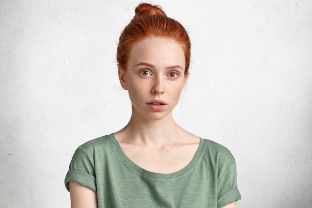 髪の結び目、健康な純粋な肌、そばかすのある肌を持つかなり生姜の女性は、カジュアルなtシャツを着ており、自信を持って真剣に見えます