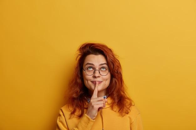 Симпатичная рыжая женщина смотрит вверх, держит указательный палец над губами, наверху у нее таинственный тайный взгляд.