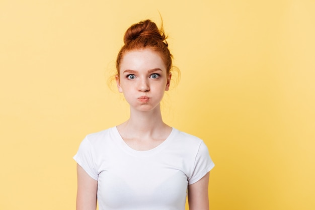 Pretty ginger woman in t-shirt with puffed cheeks