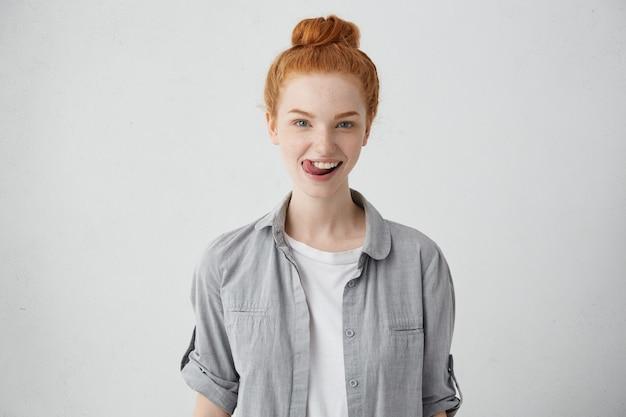 Симпатичная рыжая женщина с голубыми глазами и веснушками в повседневной рубашке развлекается, прикасаясь языком к зубам со счастливым выражением лица