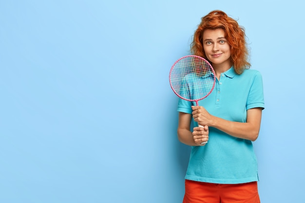 Pretty ginger woman with curly hair, likes tennis, holds racket, ready for playing, wears casual summer outfit