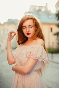 裸の肩を持つ白いドレスを着ている長い髪のかわいい生姜の女性