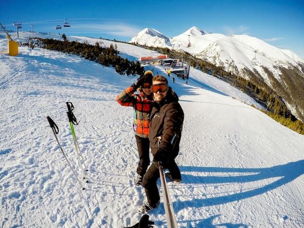 Красивая девушка и мужчина, делающий улыбающееся фото с селфи-палкой на горе, покрытой снегом.