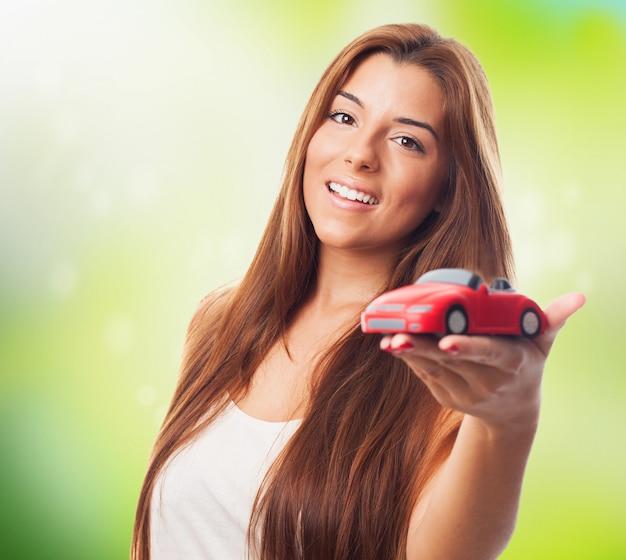 かわいい女の子と赤のおもちゃの車。