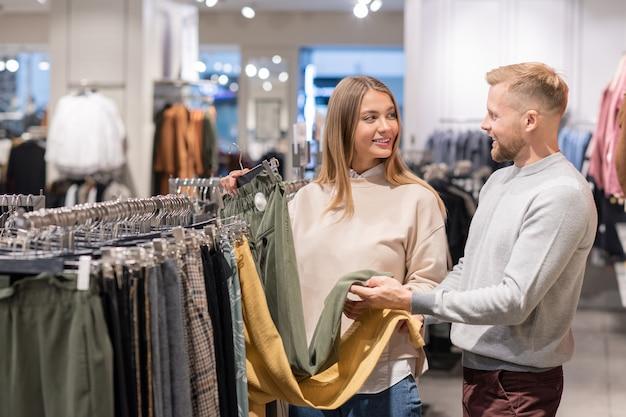 きれいな女の子と若い男がモールでの販売中に新しいパンツのペアを購入しようとしているときに黄色と灰色の色の間で選択
