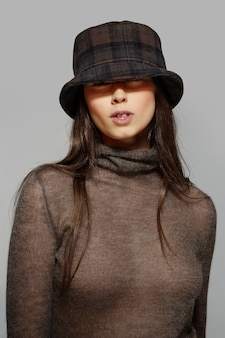 Pretty girl in angora sweater and hat in squares