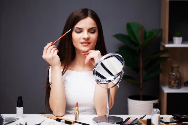 かわいい女の子が自宅の鏡の近くの顔に化粧を適用します。