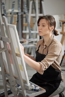 Pretty girl in apron looking at unfinished painting while sitting in front of easel with picture and drawing at lesson
