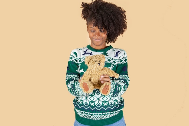 テディベージュの背景を持つクリスマスのかわいい女の子