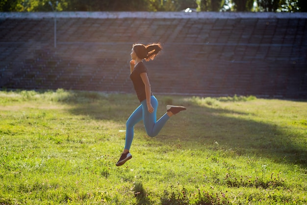 トレーニング中にジャンプするスポーツアパレルのかわいい女の子のアスリート。テキスト用のスペース