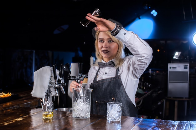 Pretty girl barman intensely finishes his creation while standing near the bar counter in bar