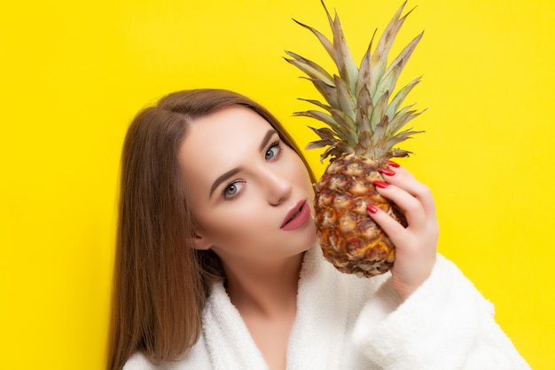 Pretty girl in a bathrobe holding a pineapple on a yellow