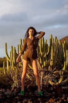 Pretty girl or beautiful woman, sexy slim brunette wearing sexi brown shirt at desert cacti in evening sunlight outdoors on grey sky background