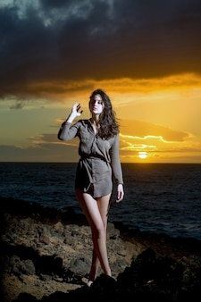 Pretty girl or beautiful woman with long brunette hair wearing sexi brown shirt standing on rocky shore at blue sea or ocean during idyllic sunset under dark cloudy sky on bright yellow sky background
