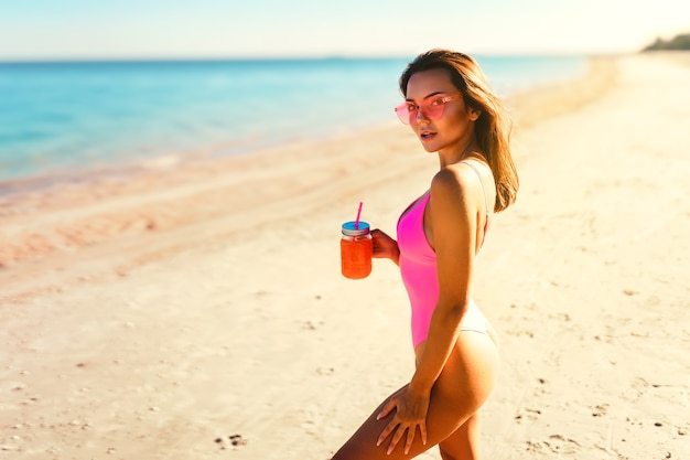Pretty girl in bikini on her perfect body walks sea white sand while holds cocktail vacation