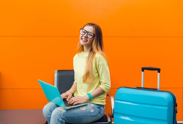 Pretty girl in black glasses with long hair is sitting on chair on orange background. she has blue laptop and suitcase. she wears yellow sweater and smiling to the camera.