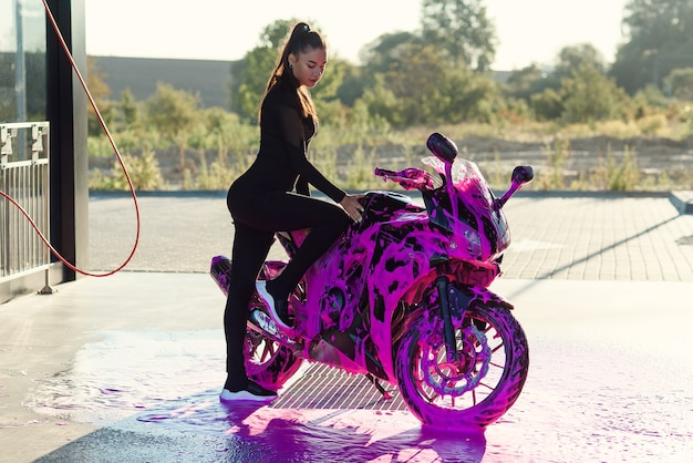 Pretty girl in black seductive suit stands near motorcycle at self-service car wash at sunrise.