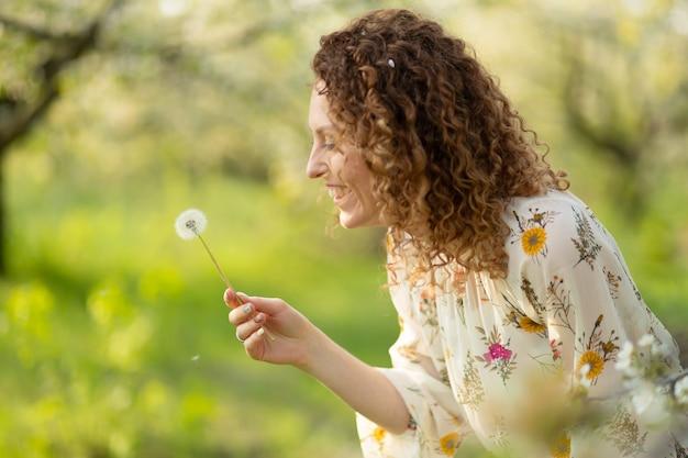 Красивая девушка дует одуванчик в парке летом. зеленая трава красивая природа. чистые эмоции.