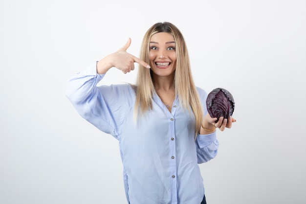 Pretty girl in blue outfit posing with single cabbage on white.