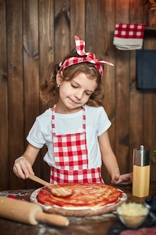 Pretty girl in checkered apron cooking pizza