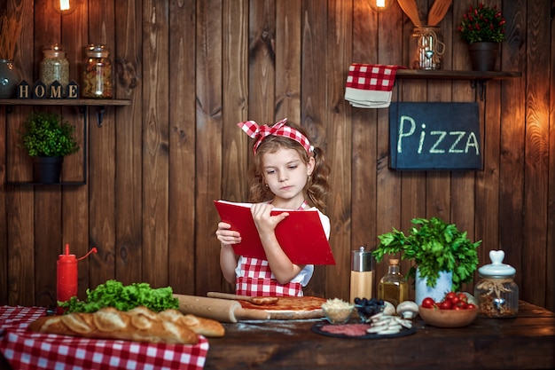Pretty girl in checkered apron reading recipes book