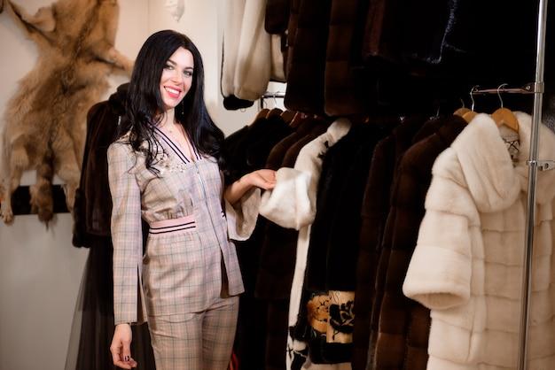 婦人服店で新しい毛皮のコートを調べるかわいい女の子の顧客