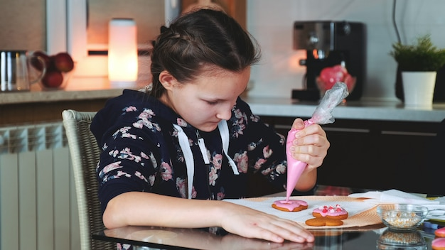 Pretty girl decorating cookies with color sugar glaze in the evening at home