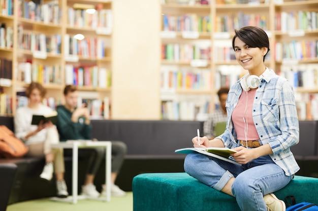公共図書館で宿題をしているかわいい女の子