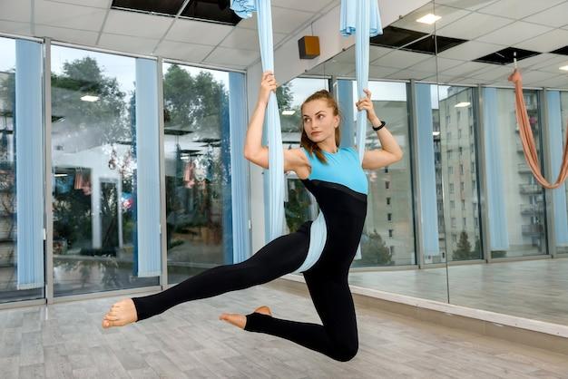 Красивая девушка делает расслабиться упражнения йоги летать в гамаках. баланс тренировки женщины в воздухе