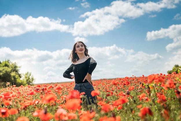 赤いポピーのフィールドで夢を見て、自然を楽しむかわいい女の子。夏の時間