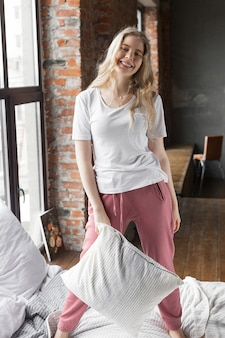 Pretty girl dressed in pink pajama pants and white t-shirt standing on a bed with a pillow near a window in loft apartment