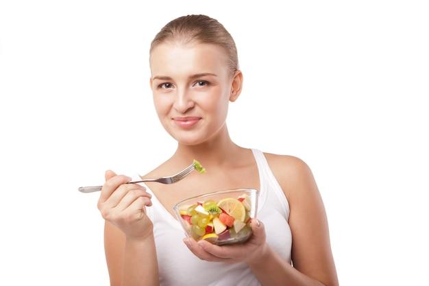 孤立したフルーツサラダを食べるかわいい女の子