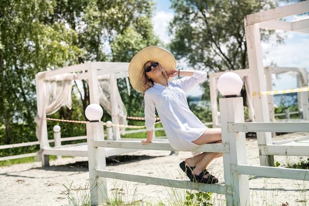 かわいい女の子は、湖の近くの白い木製の望楼で晴れた日に自然を楽しんでいます。自由