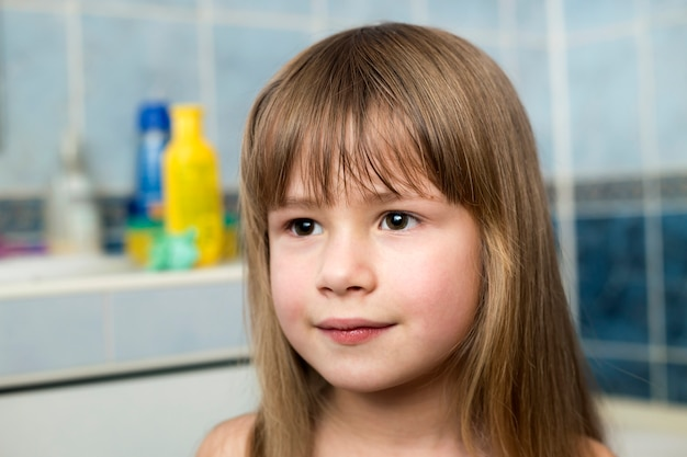 Pretty girl face portrait, smiling child with beautiful eyes and long wet fair hair