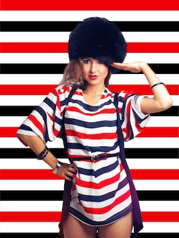 Pretty girl in furhat on stripes background