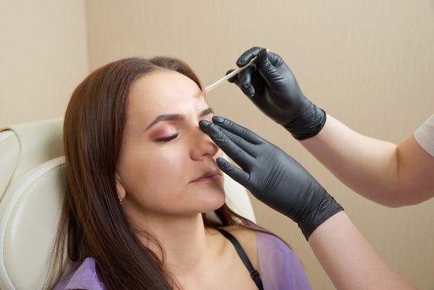 Pretty girl getting brow waxing in beauty salon