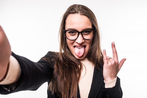 Pretty girl in glasses shows rock sign and tongue out isolated on white