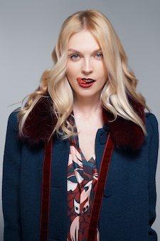 Pretty girl going crazy alone, showing long tongue, heeky mood. portrait of lady in coat with fur collar.