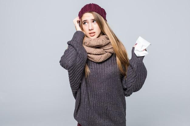 Pretty girl in grey sweater is cold had flu headache on gray